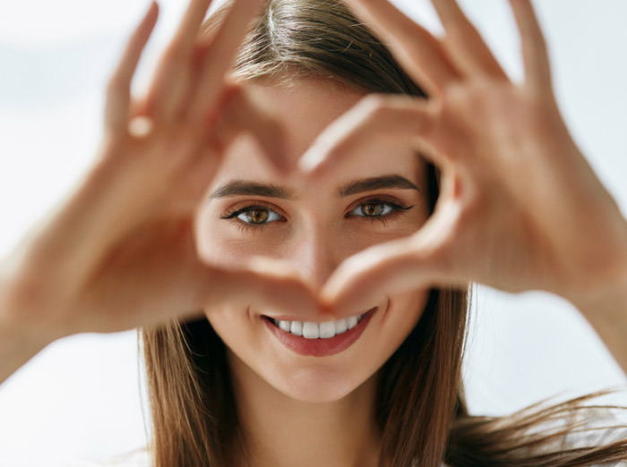 A woman looking at the camera through her hands shaped like a heart