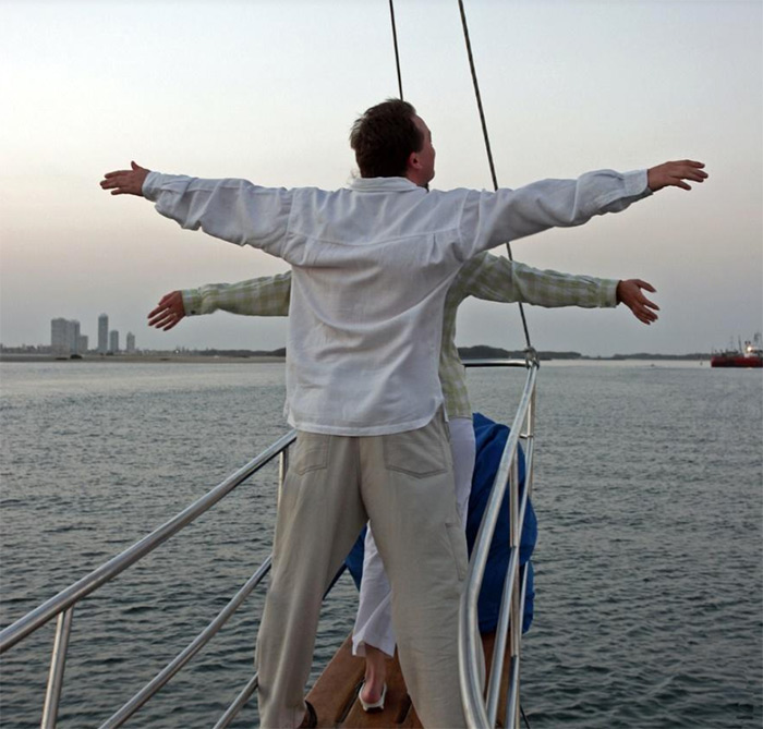 2 people in front of boat with arms outstretched