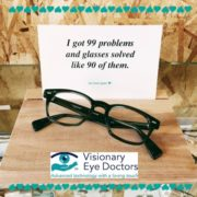 """Glasses in front of a sign reading """"I got 99 problems and glasses solved like 90 of them."""""""