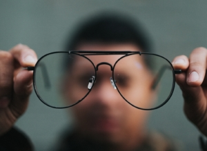 Blurred image of a man holding up glasses.