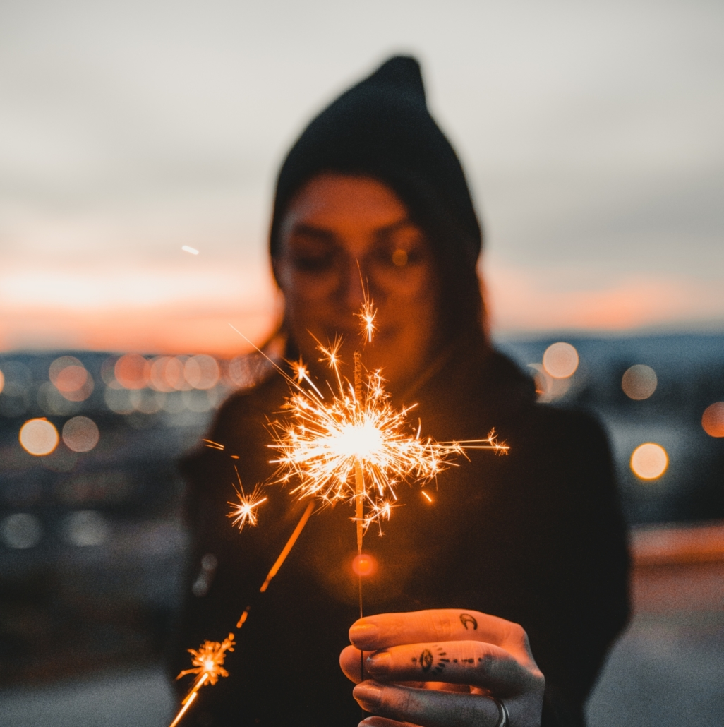 Woman in hoodie wearing glasses and playing with sparkler.