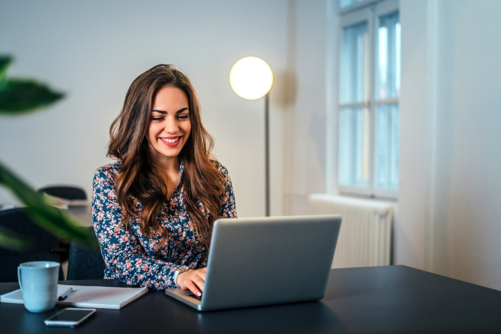 Cheerful woman using laptop for televisit.